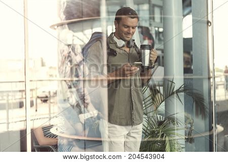 Joyful adult male traveler with headphone and backpack is sending message using smartphone. He is standing at airport and drinking coffee while expressing happiness. View from glass window