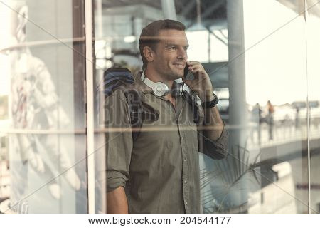 Enjoying conversation. Happy adult bristled man with backpack and headphones is talking on mobile phone while looking out through window glass. He is waiting for his flight