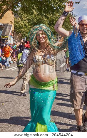 SEATTLE, USA - JUNE 22, 2013: An unidentified pregnant woman in a mermaid costume smiles as she walks down the street in the annual Fremont Summer Solstice Parade in Seattle.