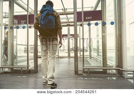 Arrival. Young traveler with backpack is exiting from airport. Back view. Copy space in the right side