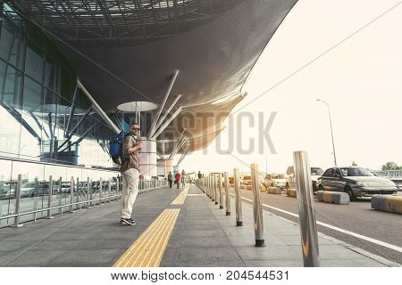 Good mood. Cheerful guy with backpack and headphones is standing near airport on street. He is looking at camera with joy. Copy space in the right side