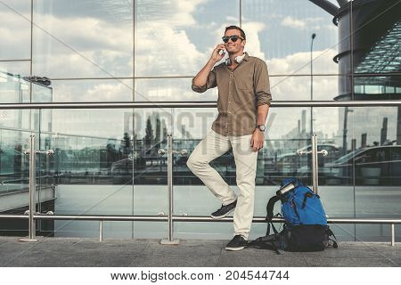Good news. Happy stylish man in sunglasses is standing outdoors near airport window. He is talking on mobile phone. Cloudy sky is reflecting in clear glass building. Copy space in the left side