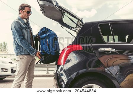 Positive man in sunglasses is putting his backpack in trunk of car. Copy space in the right side