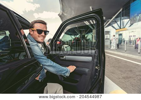 Joyful stylish man is opening door of auto and peeking out from car. He is looking at camera with smile. Airport building on background. Copy space on the right side