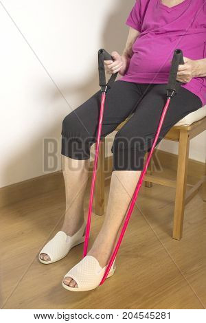 Rehabilitation exercises with elastic resistance rubber for older woman with cerebral stroke