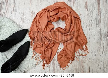 Fashionable Concept. Large Scarf And Black Boots. Top View, Light Wooden Background