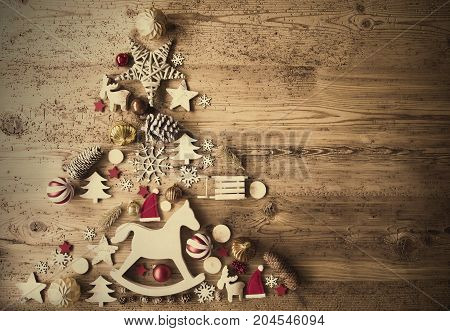 Christmas Decoration Forming Shape Of Christmas Tree. Decoration Like, Rocking Horse, Santa Hat, Fri Con And Christmas Ball Ornament. Retro Brown Wooden Background With Copy Space