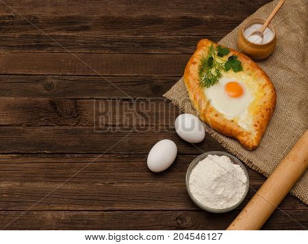 Khachapuri With Eggs On Sackcloth, Salt, Flour, Eggs And Parsley On The Wooden Table, Space For Text