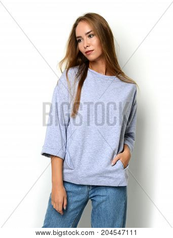 Young happy beautiful woman posing in new fashion blue jeans and pullover with text copy space on a white background