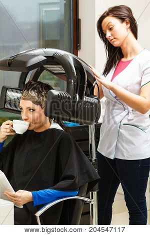 Haircare relaxation and hairstyling concept. Woman sitting in black cape getting her hair dried under machine