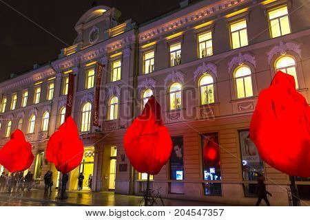 VIlnius, Lithuania - January 01, 2017: Unknown people go along street Gediminas Avenue in Old Town, Vilnius at Lithuania at night