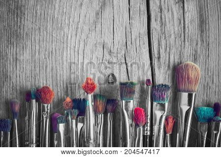 Row Of Artist Paintbrushes With Colorful Bristle Closeup On Old Wooden Background, Retro Black And W