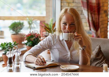 young blonde caucasian woman with happy smile i is drinking coffee at day time