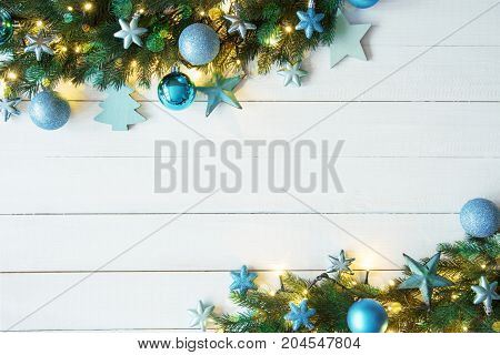 White Wooden Background With Copy Space. Christmas Banner With Turquoise Frame Christmas Decoration Like Balls, Star. Fir Branches With Fairy Lights And Bokeh Effect.