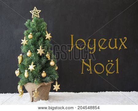 French Text Joyeux Noel Means Merry Christmas. Golden Decorated Christmas Tree With Black Concrete Or Cement Background. Modern Urban Style With Snow