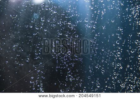Rain drops on the glass on a blue background. Design Element