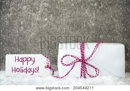 One White Gift With Label With English Text Happy Holidays. Gray Grungy Cement Background With Snow And Snowflakes.