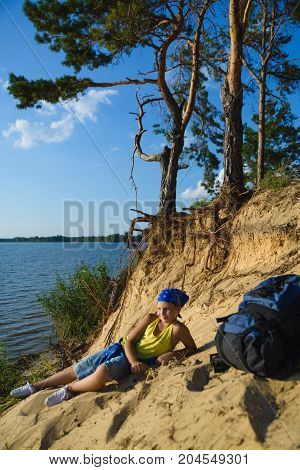 Boy sitting on sand cliff looking to sea. Travel and tourism concept.