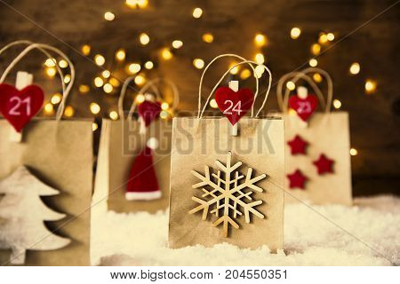 Christmas Shopping Bag With Numbers 21 to 24 On Snow. Decoration Like Santa Claus Hat, Snowflake, Christmas Tree And Stars. Fairy Lights In Background And Instagram Filter