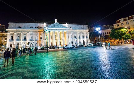 Lisbon, Portugal - August 24, 2017: The National Theater D. Maria II illuminated by night in Praca Dom Pedro IV or Rossio Square in Lisbon downtown.Rossio Square is a popular place for evening parties