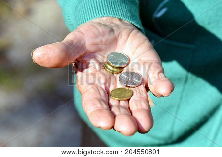 The coins are in the hands of the old lady. An elderly woman with money in her hands. Poverty alms.