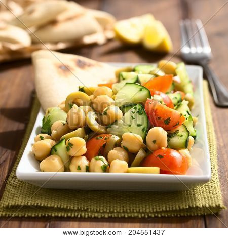 Chickpea salad with green olives cucumber cherry tomato and parsley served on plate with pita bread pieces in the back photographed with natural light (Selective Focus Focus one third into the salad)