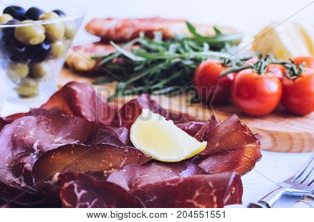 Slices of Italian meat Bresaola served with olive oil and lemon on a plate with tomatoes and bread on white background. Traditional appetizers antipasti. Top view.