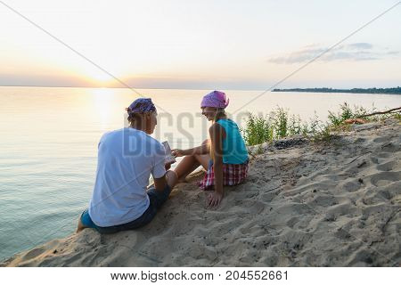 Father and daughter resting and looking at map. Adventure or travel and tourism concept.