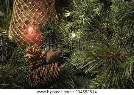 Christmas decor background close up with red candle holder, pine cones and mouse surrounded by greenery