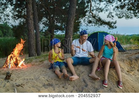 happy family roasting sausages over campfire. camping and tourism concept.
