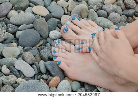 Female Feet And Hands With A Blue Manicure On Pebbles