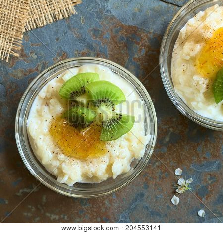Rice pudding with kiwi pieces orange jam and cinnamon in small glass bowl photographed overhead on slate with natural light