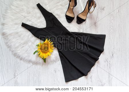 Black Short And Shoes On White Fur Sunflowers. Fashionable Concept