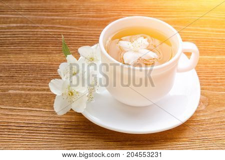 White Mug Of Tea With Jasmine On A Wooden Table. Close Up, Sunlight