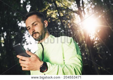 Pensive Bearded Athlete With Bluetooth Headphones And Smart Watch Looks On Smartphone And Analyzing