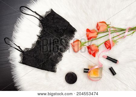 Black Lace Top On White Fur And A Bouquet Of Orange Roses And Cosmetic. Fashionable Concept. Top Vie