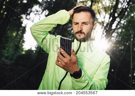 Bearded Pensive Athlete With Bluetooth Headphones Looks At Smartphone Screen With Workout Sport Stat