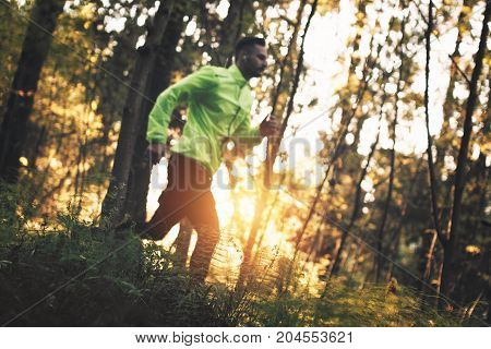 Young Athlete Runs Across Rough Terrain In Forest Through Obstacles. Deliberately Defocused Main Obj