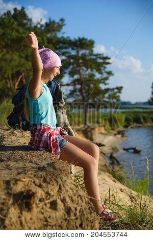 Teen girl sitting on sand cliff looking to sea. Travel and tourism concept.
