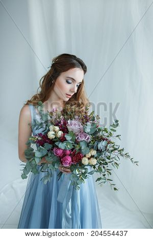 Young woman holding in hands beautiful flower bouquet