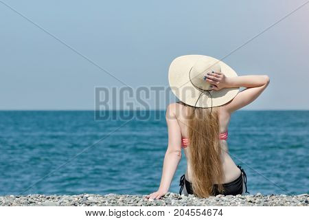 Beautiful Girl In A Hat And Swimsuit Sits On The Beach. Sea And Sky On The Background. View From The