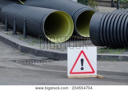 Replacement of pipes in the city. Large new pipes. Caution sign