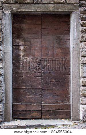 Ancient wooden door in stone wall background