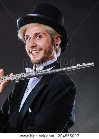 Classical music passion and hobby concept. Elegantly dressed musician man holding flute wearing black hat. Studio shot on dark background