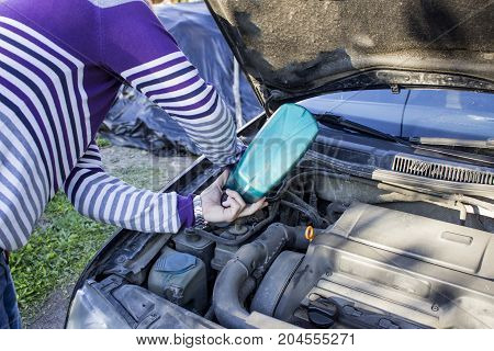 A man puts oil in the car the hood is open a breakage in the way