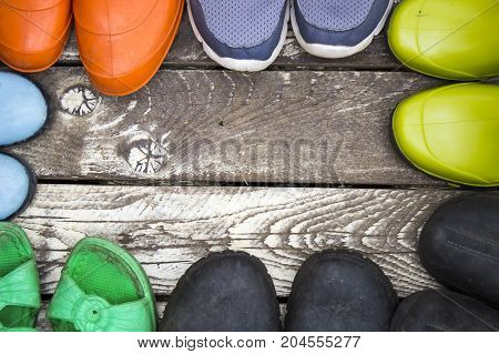 Many pairs of summer shoes: Rubber boots slippers galoshes on a vintage wooden floor space for text