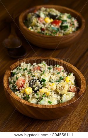 Quinoa salad with sweet corn olive tomato cucumber and chives in wooden bowl photographed on dark wood with natural light (Selective Focus Focus in the middle of the salad)