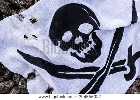 Pirate flag on the stones. Old scorched shabby. Danger. Sea.