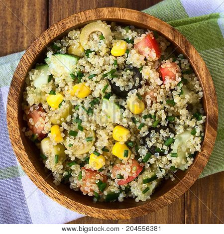Quinoa salad with sweet corn olive tomato cucumber and chives in wooden bowl photographed overhead with natural light (Selective Focus Focus on the top of the salad)