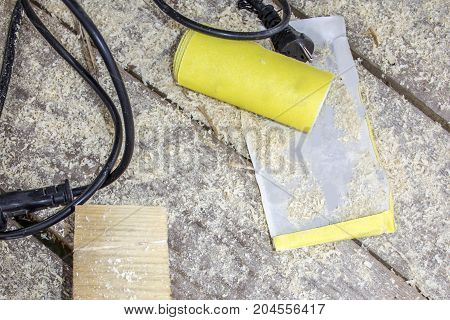 Yellow Abrasive paper on wooden background, top view
